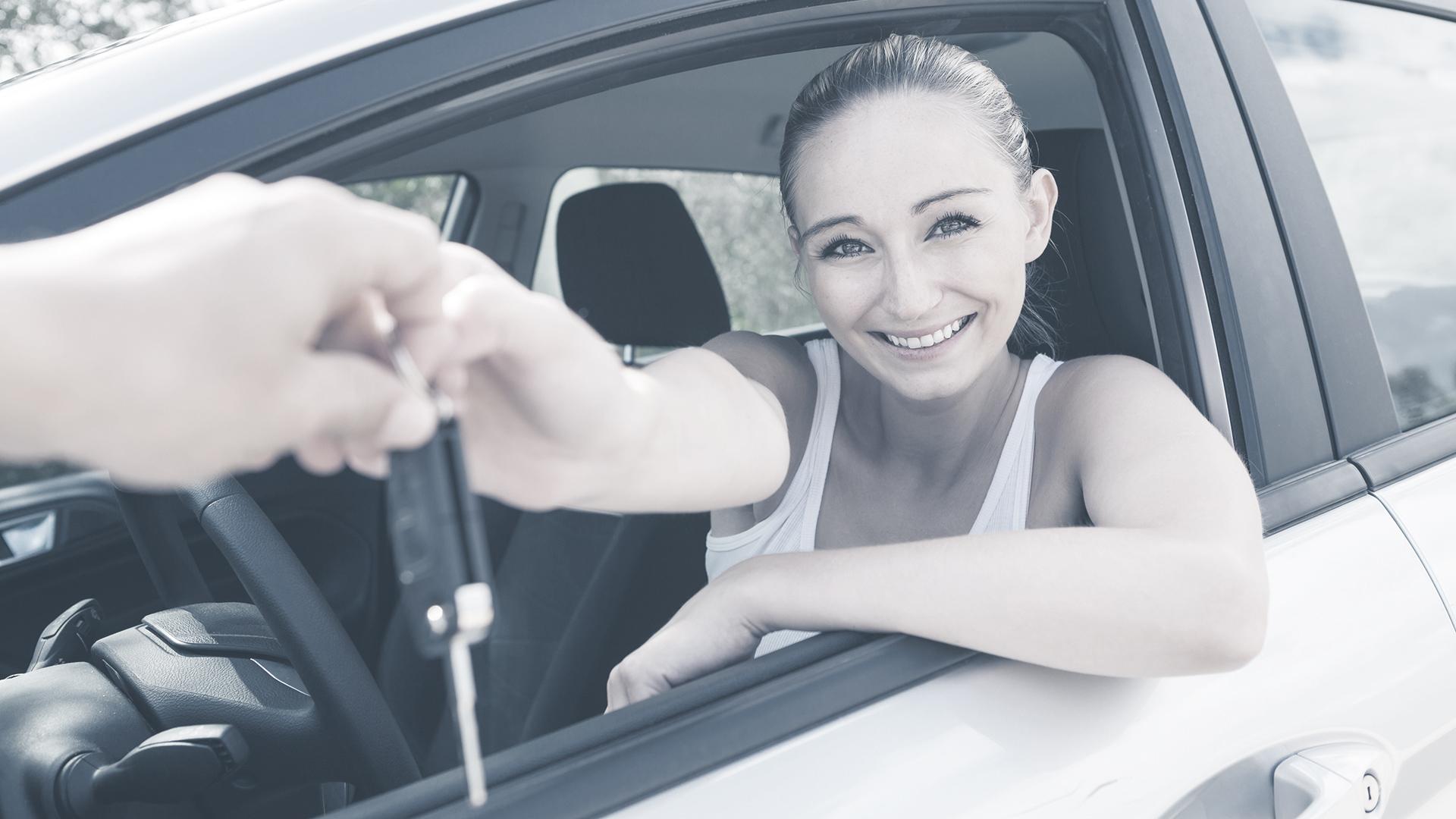 junge frau im neuen auto schlüssel übergabe lachend